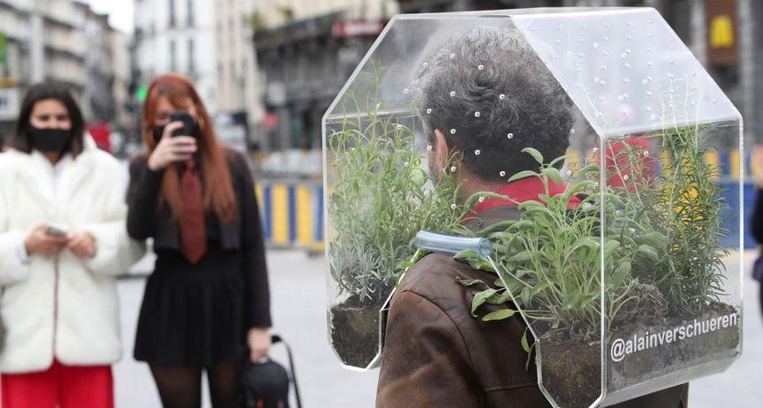 Umjesto s maskom briselski umjetnik gradom šeće s mini staklenikom na ramenima
